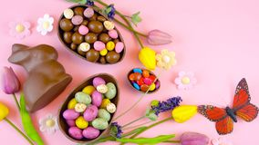 Happy Easter overhead with chocolate Easter eggs and decorations and copy space. Stock Photos
