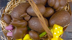 Happy Easter overhead stacking chocolate Easter eggs in basket. stock video