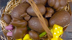 Happy Easter overhead stacking chocolate Easter eggs in basket. stock video footage