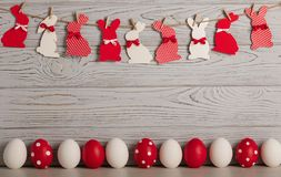 Happy Easter! Painted Easter eggs and Easter decoration - Easter bunnies with ribbons - red, white and red with white polka dots. Happy Easter! Painted Easter stock photography