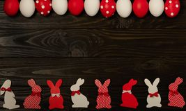 Happy Easter! Painted Easter eggs and Easter decoration - Easter bunnies with ribbons - red, white and red with white polka dots stock images