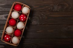 Happy Easter! Painted Easter eggs - red, white and red with white polka dots on a brown wooden background royalty free stock photos