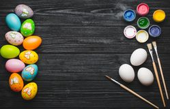 Painting eggs for Easter holiday on wooden table Royalty Free Stock Image