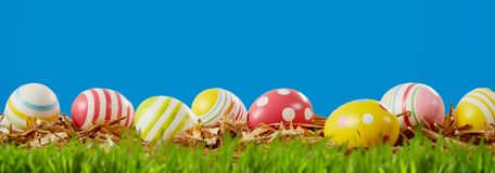 Happy Easter panorama banner with eggs in a meadow. Happy Easter panorama banner with colorful decorative eggs nestling on the green grass in a meadow under a royalty free stock photo