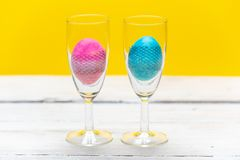 Happy Easter - pastel blue and pink egg in a glass of champagne on a bright, spring background stock images