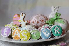 Happy easter pastel eastereggs bunny cookies table lace words alphabet greeting message. Holiday celebration cute pink plate spring wood stock photos