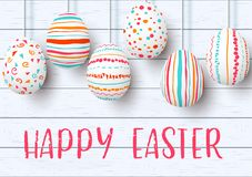 Happy Easter. pending easter eggs on white wooden background. Easter colorful hanging. Eggs with simple pink, orange, red, blue stripes, patterns, ornaments Royalty Free Stock Images