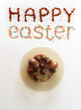 Happy Easter phrase made from raisins and colorful baking sugar over white background with a plate full of chocolate eggs and cand Royalty Free Stock Image