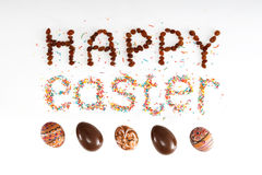 Happy Easter phrase made from raisins and colorful baking sugar over white background with row of colorful hand drawn eggs and cho Royalty Free Stock Photo