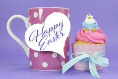 Happy Easter pink, yellow and blue cupcake with coffee. Happy Easter pink, yellow and blue cupcake with cute chicken decorations on purple background and pink Stock Photos