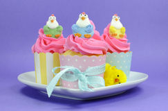 Happy Easter pink, yellow and blue cupcakes with cute chicken decorations Stock Photos