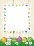 Happy Easter Poster with copy space. Happy Easter greeting Card, painted eggs in grass, white board wih copy space, wood background Royalty Free Stock Image