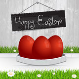 Happy Easter. Red Easter eggs.The grass with a wooden fence and Stock Photos