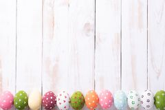Happy easter! Row Easter eggs with colorful paper flowers on white wooden background royalty free stock photography