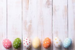 Happy easter! Row Easter eggs with colorful paper flowers on white wooden background royalty free stock images