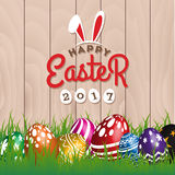 Happy Easter Season`s Greeting Card 2017. Painting Eggs Hidden on Grass With Easter Typographic Background. Vector illustration Stock Photography