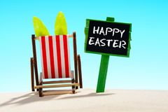 Happy Easter poster and Bunny relax on sun loungers on the sandy beach. Happy Easter sign and Bunny relax on the sun loungers on the sandy beach royalty free stock image