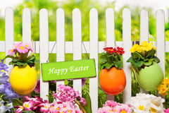 Happy Easter. Sign Happy Easter hangs on the garden fence royalty free stock photos