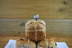 Happy Easter sign held by a miniature person figurine standing on some fresh hot cross buns. Homemade fresh baked hot cross buns for Eastertime on a white table Royalty Free Stock Photos