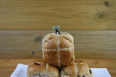 Happy Easter sign held by a miniature person figurine standing on some fresh hot cross buns. Homemade fresh baked hot cross buns for Eastertime on a white table stock photos
