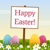 Happy Easter Sign in a Meadow with Eggs Stock Photos