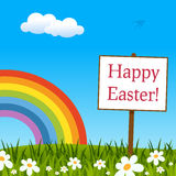 Happy Easter Sign in Meadow with Rainbow Royalty Free Stock Image