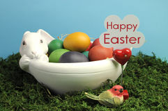 Happy Easter sign with white bunny rabbit bowl of eggs. Happy Easter rainbow colored eggs on grass against a blue sky background Royalty Free Stock Photos