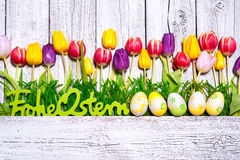 Happy Easter. Spring tulips with Easter eggs and german text on wooden background. Background for Easter stock photos