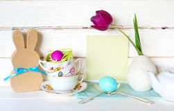 Happy Easter Tea Party or Meal Invite Card with Tea Cups, Bunny, Flower, Egg and Silverware in Modern Whimsical Arrangement. With Shiplap Board Background. Wide royalty free stock photos