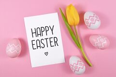 `Happy Easter` text card surrounded by easter eggs and single yellow tulip spring flower on pink colored background, flat lay