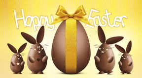 Happy easter text with chocolate egg and bunnies on yellow Stock Photos