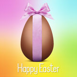 Happy easter text with chocolate egg and pink ribbon bow Royalty Free Stock Image