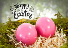 Happy Easter text with Easter eggs in nest in forest Stock Photography