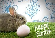Happy Easter text with Easter rabbit with egg in front of pattern Stock Image