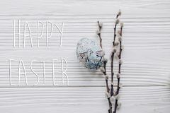 Happy easter text greeting card sign on simple easter egg with c. Hick ornaments and willow buds on rustic white wooden desk background. with space for text, top Stock Photos