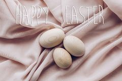 Happy easter text greeting card sign on simple wooden easter egg. S for decoration on fabric and rustic white wooden desk. eco concept with space for text, top Stock Image