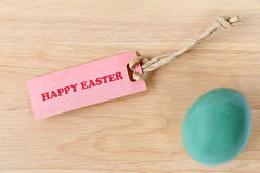 Happy Easter text on paper tag with an easter egg on wood background Stock Image