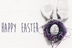 Happy Easter text. season`s greetings card. bunny ears and styli. Sh egg in nest on white wooden background flat lay. happy easter concept Stock Photo