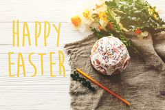 Happy easter text. season`s greetings card. stylish  easter cake. On rustic wooden background with spring flowers and candle, top view. space for text.  modern Royalty Free Stock Photography