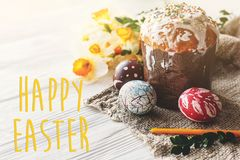 Happy easter text. season`s greetings card.  stylish painted egg. S and easter cake on white rustic wooden background with spring flowers and candle.  modern Stock Photo