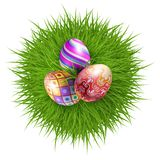 Happy Easter. Three Brightly Colored Easter Eggs on a Round Patch of Green Grass Over White Background to Celebrate the Festive Season Royalty Free Stock Images