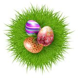 Happy Easter. Three Brightly Colored Easter Eggs on a Round Patch of Green Grass Over white to Celebrate the Festive Season Royalty Free Stock Photos