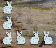 Happy easter white bunnies on wooden background copyspace. White esater bunnies lined up at the side and base of wooden copyspace, facing the same direction or Stock Images