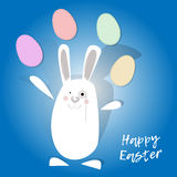 Happy easter. White rabbit juggling easter eggs. Blue background. Royalty Free Stock Photos