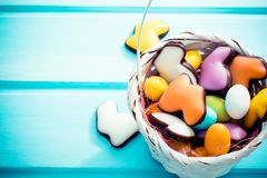 Happy Easter. White straw basket full of colorfull sweets eggs and rabbits on light blue background. Copyspace. stock photo