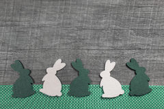 Happy easter: wooden background with green and white rabbits for Stock Image