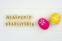 Happy Easter wooden blocks with Easter eggs on white wood Stock Photo