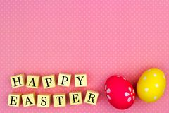 Happy Easter wooden blocks with eggs on pink background Stock Photo