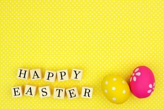 Happy Easter wooden blocks with eggs on yellow background Stock Photos