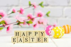 Happy Easter wooden blocks with flowers and eggs Royalty Free Stock Photos